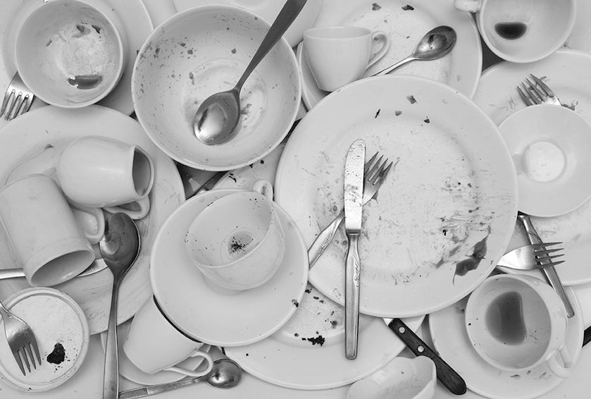 Black and White image of a collection of dirty plates bowls cups saucers and cutlery