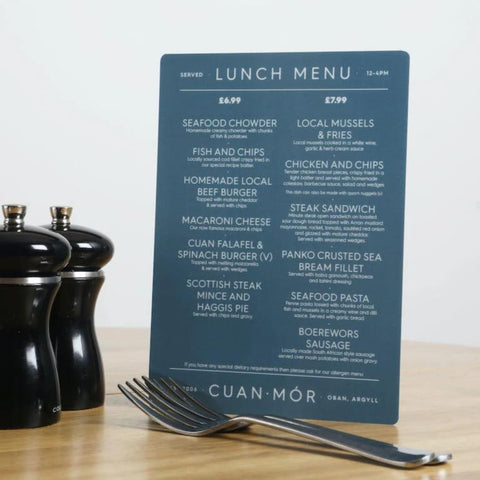 A5 portrait blue lunch menu on a table beside pepper grinder and cutlery to show scale