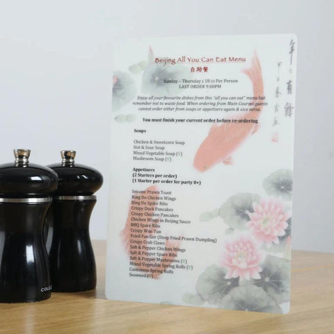 A5 Oriental Buffet menu on a table beside pepper grinders to show scale
