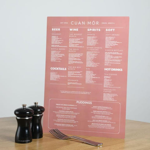 A portrait image of a pink and white long lasting SuperTuffMenu beside the menu sits some cutlery and salt and peppers grinder to give the size context