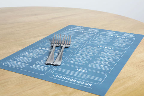 an image of a blue and white wipeable SuperTuffMenu on a table lying on the menu are some forks to give size context