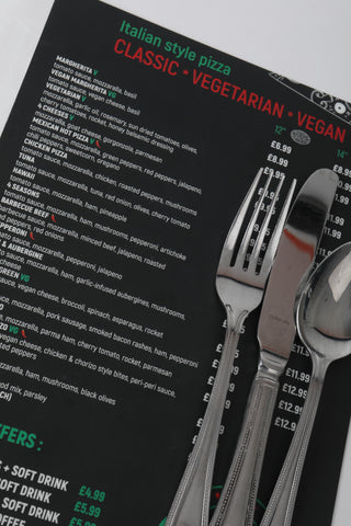Section of menu black background with white green and red text with cutlery for scale