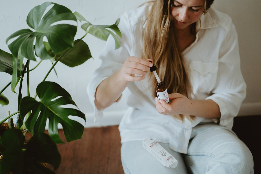 Woman in white using CBD tincture with dropper
