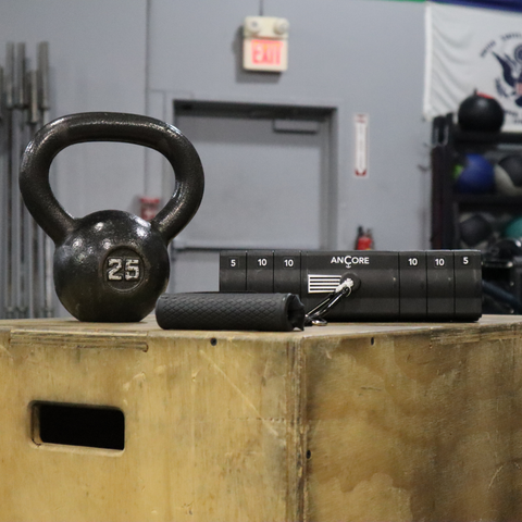 the ancore trainer next to a kettle bell to show how much space it saves