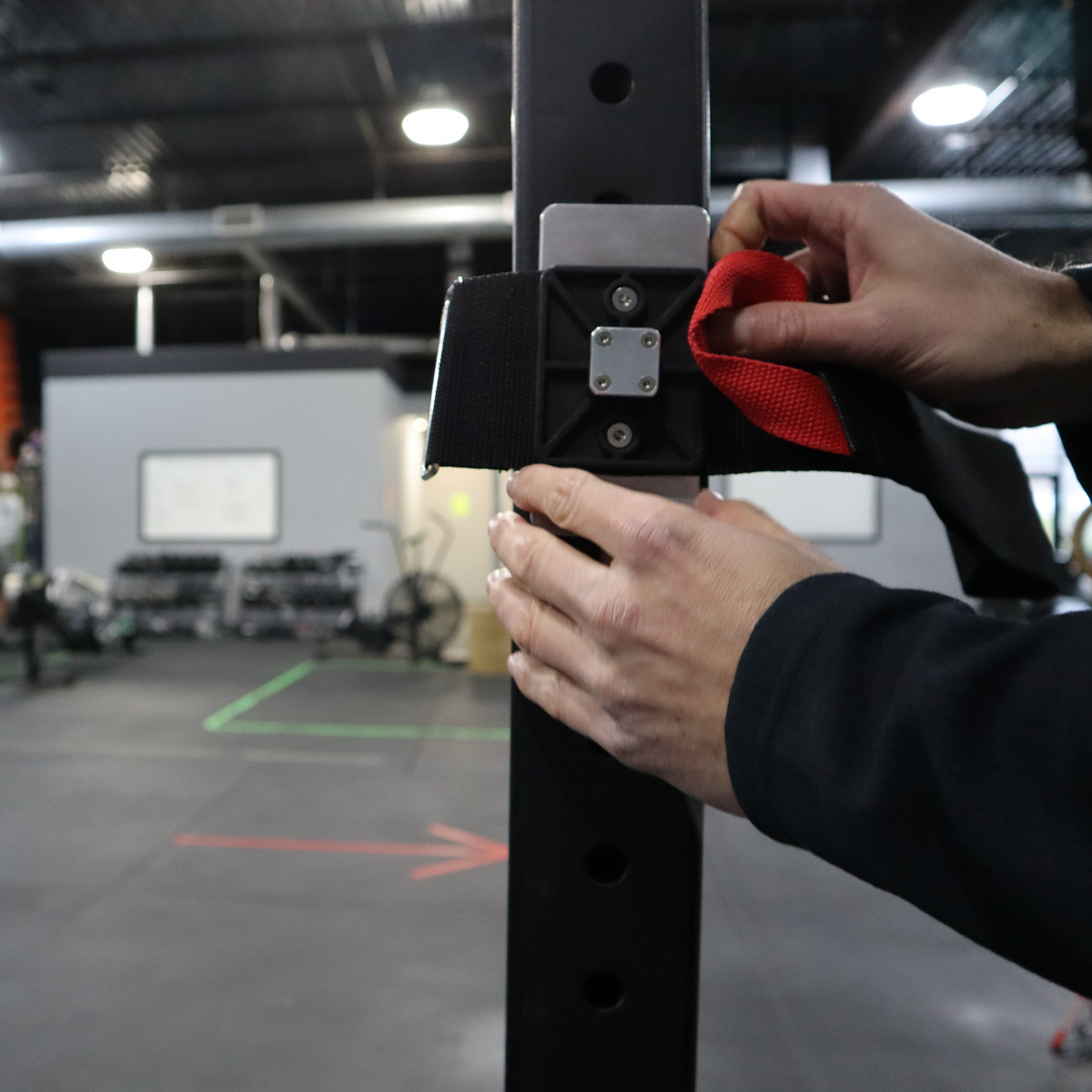 an athlete setting up the ancore rack mount strapping around a squat rack