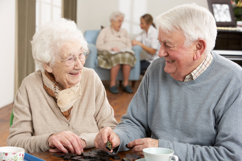 Elderly Couple Playing Dominoes in Senior Home