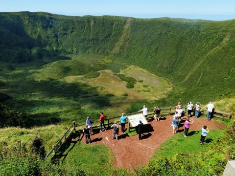Tourists looking at a volcanic crater on the Faial island in the Azores Portugal