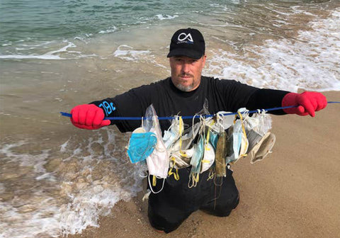 Gary Stokes, co-founder of OceansAsia, holds up the masks he found strewn across beaches near Hong Kong in February 2020 (OceansAsia)