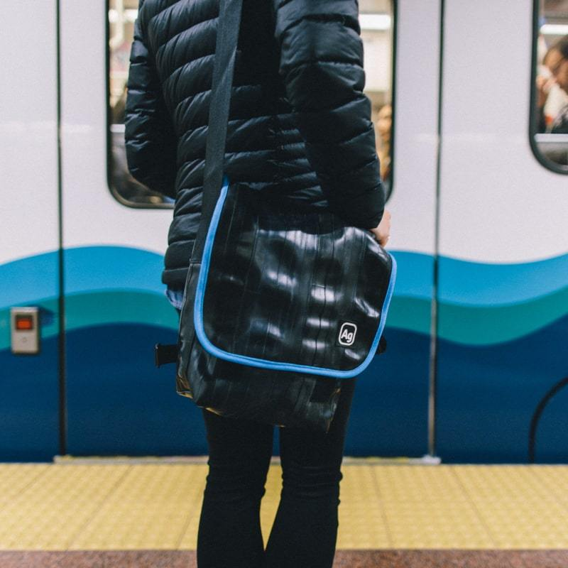Person wearing the Alchemy Goods Haversack Shoulder Bag satchel with turquoise accents with front of a train