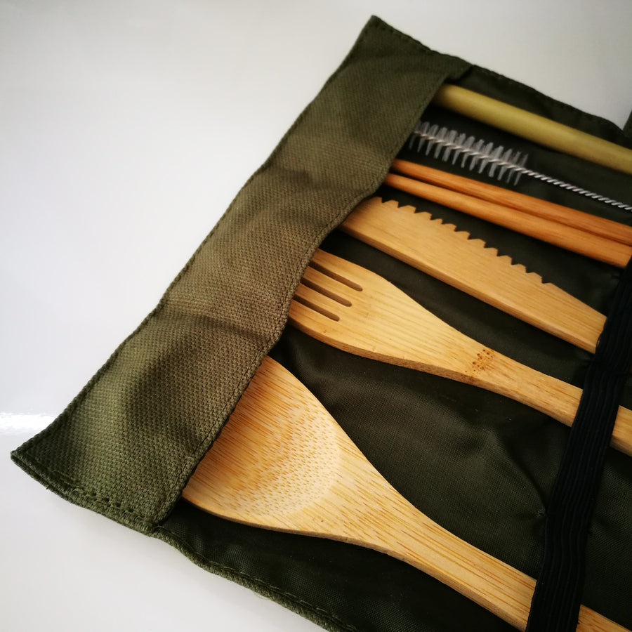 Detail of seven piece bamboo cutlery set with knife, fork, spoon, chopsticks, straw and brush cleaner in a green canvas pouch.