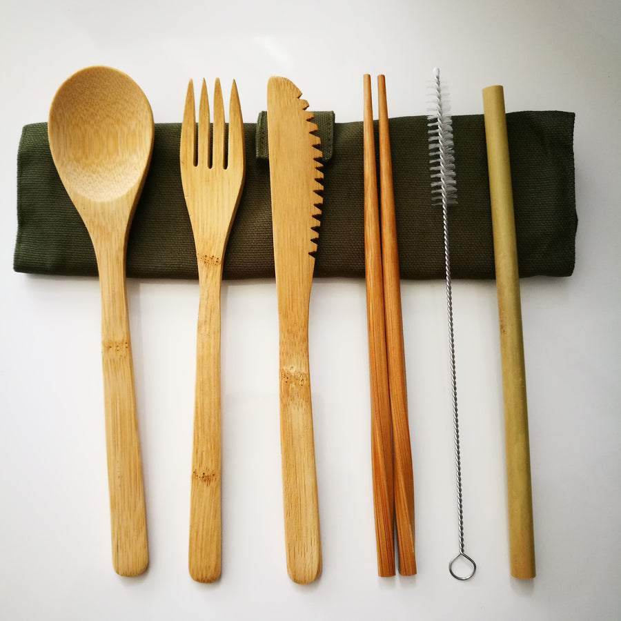 Seven piece bamboo cutlery set with knife, fork, spoon, chopsticks, straw and brush cleaner on a rolled up green canvas pouch.