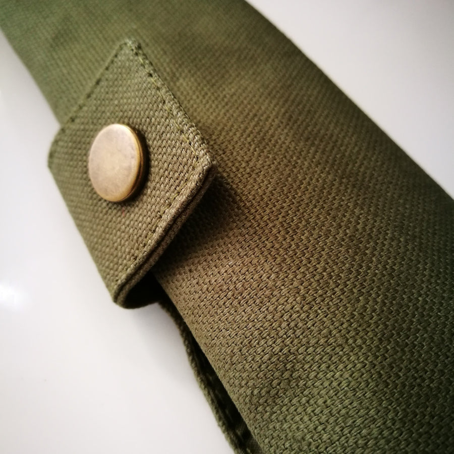 Close up of snap enclosure on green canvas roll-up pouch for bamboo cutlery.