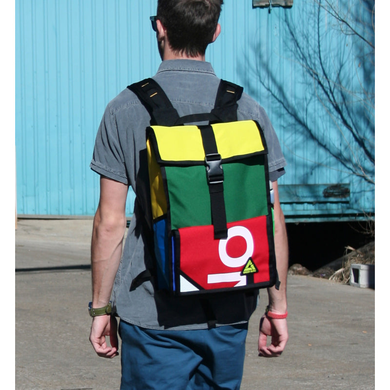 Back view of a man wearing roll top backpack