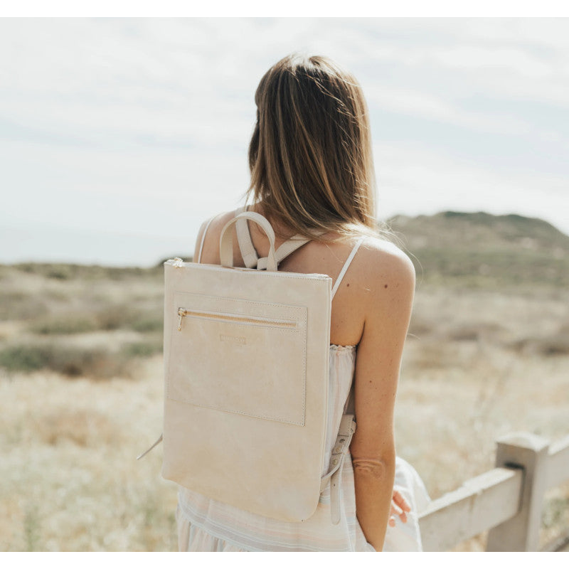 Back of a woman wearing the Miramar Leather Backpack in bone color