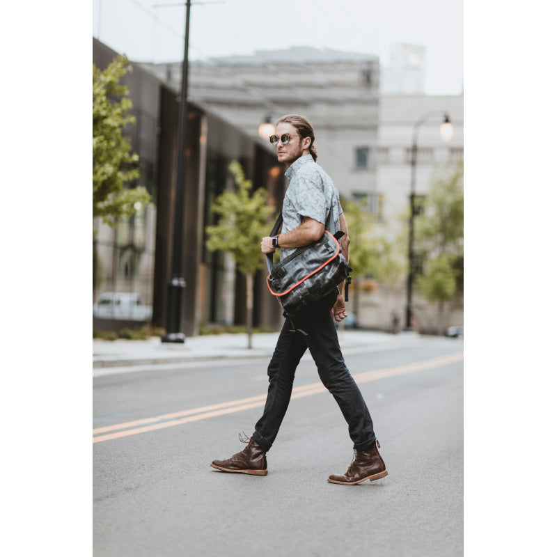Man wearing sunglasses  holding the Alchemy Goods Pike Messenger Bag with red accents
