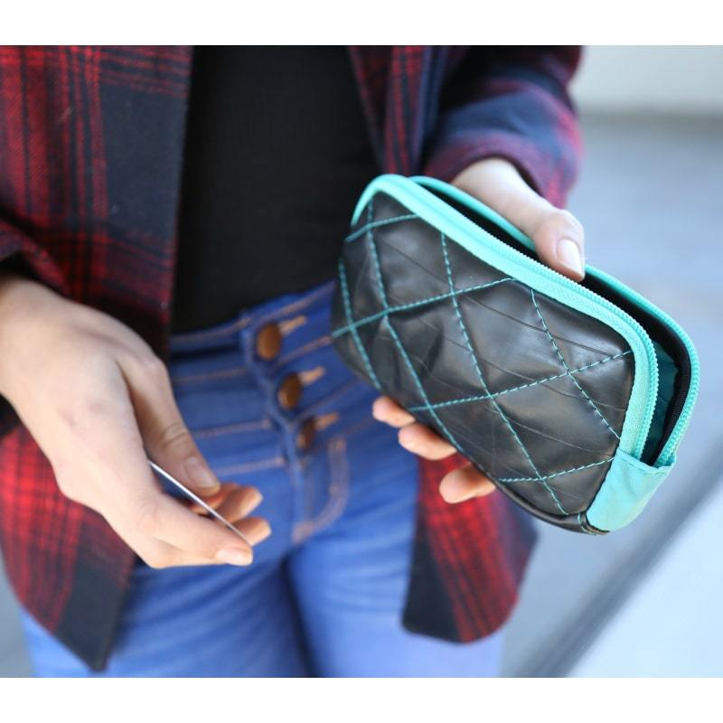 Woman holding in her left hand the Alchemy Goods Roxhill zip wallet with turquoise accents