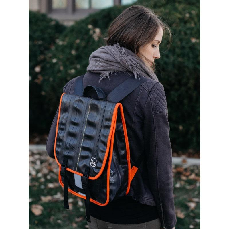 Woman wearing the Alchemy Goods Madison laptop backpack with orange accents