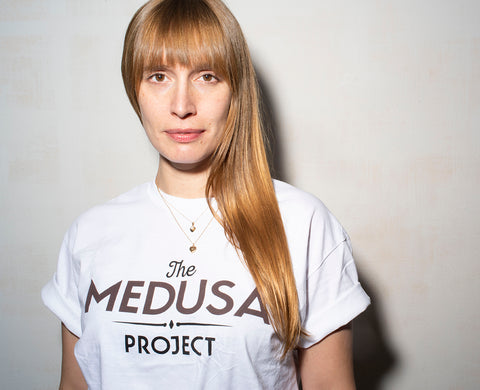 Waist up portrait of woman with ginger hair in a Medusa Project tee.
