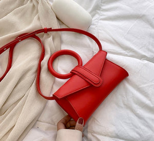 Mini vegan leather bag in red orange color  with circular handle and detachable strap in the same color