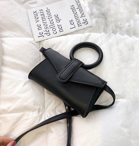 Mini vegan leather bag in black color with circular handle and detachable strap in the same color