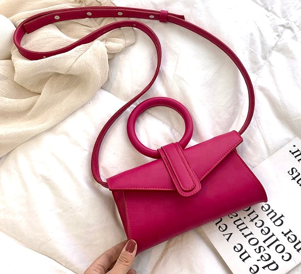 Mini vegan leather bag in fuchsia pink with circular handle and detachable strap in the same color