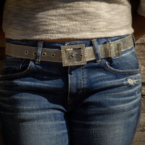 woman in denim pants wearing a metallic belt with crystal inlays on the buckle