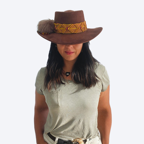 black-haired model wearing chocolate brown suede hat with handmade woven band in yellow