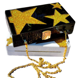Black acrylic bag box with gold color stars and a gold  metal chain  on top of another bag same style but in white color