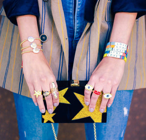 model holding an acrylic bag with gold stars on black wearing colorful rings and gold and multicolored bracelets
