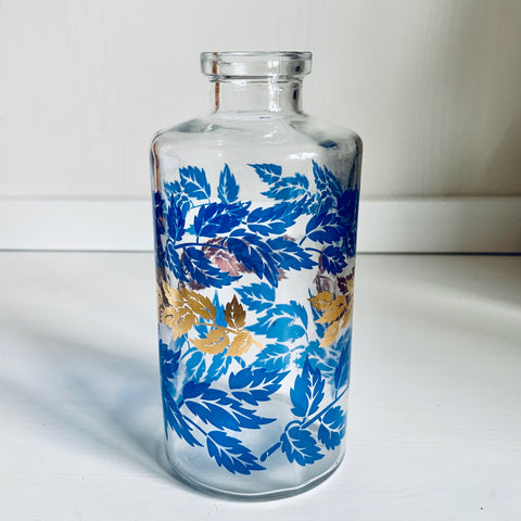 Glass bottle with leaf decoration