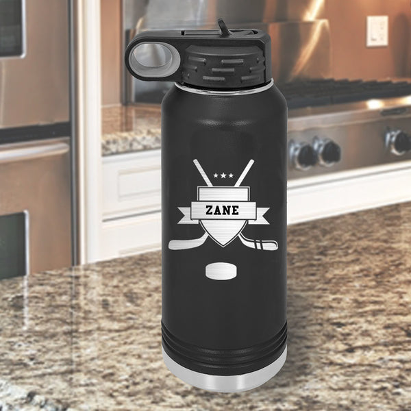 32 ounce water bottle black with hockey crossed sticks crest and puck name in ribbon of crest