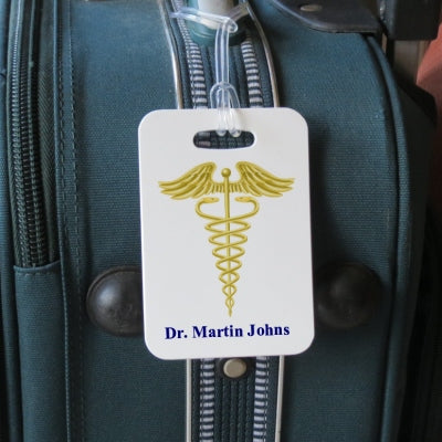 luggage tag shown on luggage with caduceus and doctors name