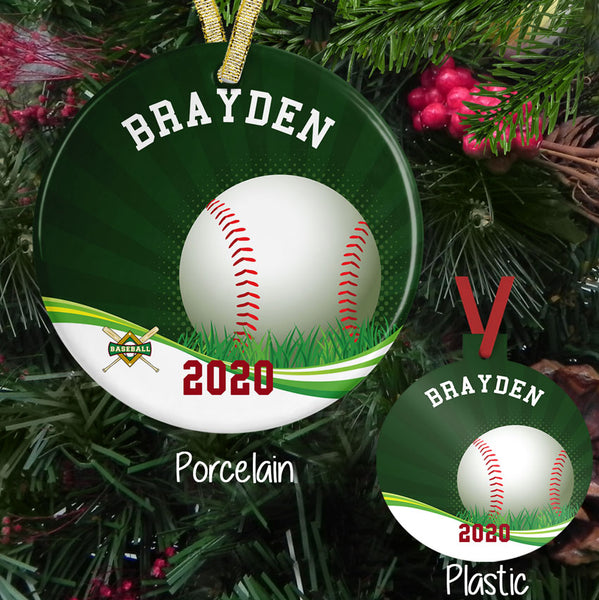 Christmas Ornament in plastic and porcelain -green sunburst backdrop with baseball sitting in grass on a swirl bottom cross bags and baseball diamond small on left bottom. Personalized with any arched text on top and straight text on bottom.