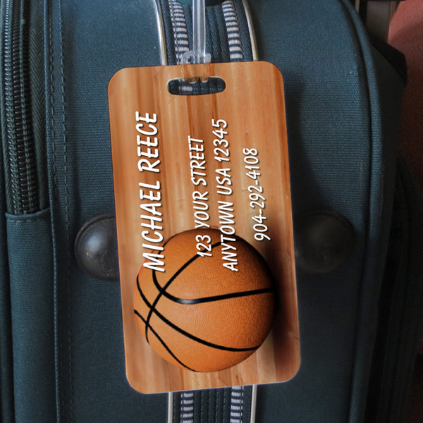 Basketball sitting on wood floor custom sports bag tag personalized with name and contact info