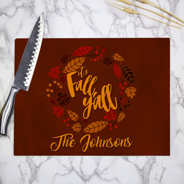 Brown background with earth tones of leaf circular border around it's Fall Y'll text and any personalized text on the bottom of a printed tempered glass cutting board