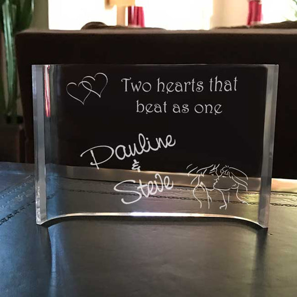 "double linked hears along with a kissing couple and text that says ""Two hearts that beat as one"". Any two names personalized on this curved clear acrylic desk plaque"