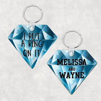 Diamond Shaped Key Ring with Blue Diamond Background 2 sided print one with names the other with I Put A Ring On It in black sports font