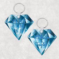 Diamond Shaped Key Ring with Blue Diamond Background 2 sided print one with names the other with SHe Put A Ring On It in Blue Text