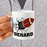 football breaking through a wall on a ceramic mug with any name personalized under the image.