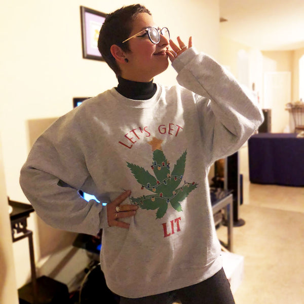 woman wearing light gray sweat shirt with pot leave as a Christmas tree shirt says lets get lit