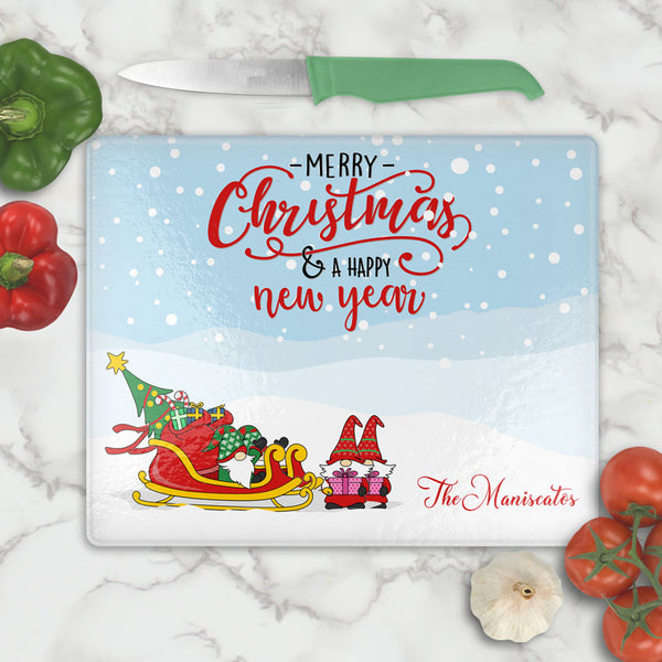 glass cutting boards with gnome elves with gift sled personalized with any name on bottom. Top says Merry Christmas and Happy New Year in Stylish font combination