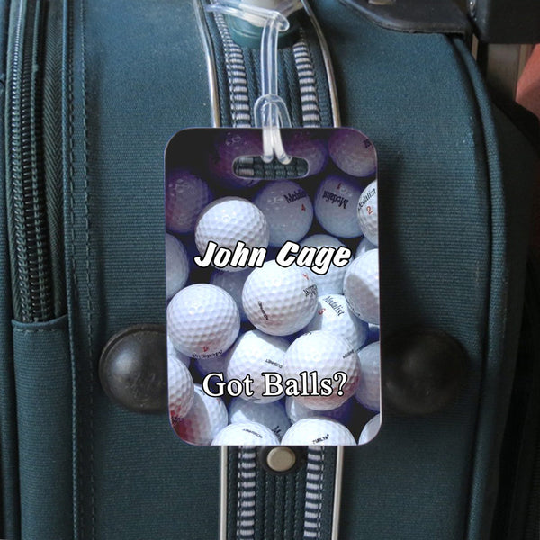 luggage tag hanging from luggage with got balls design for golfers