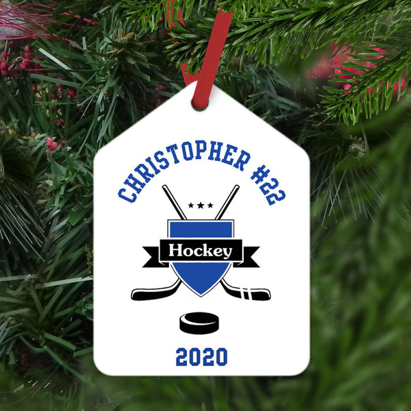 Hockey Crest with cross sticks and puck personalized with name and number arched on top and year on the bottom White ornament with blue and black  image