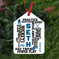 Randomly placed words about hockey on a gift tag shaped christmas ornament personalized with name jersey number and year.