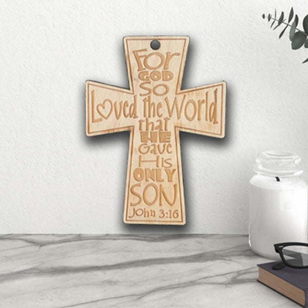 Wood Engraved Cross with John 3:16 quote  and hole on top for hanging shown against a wall near a counter