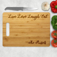 Live Love Laugh Eat is engraved across the top of this bamboo cutting board with inner loop hole handle bamboo cutting board and your name along the bottom right