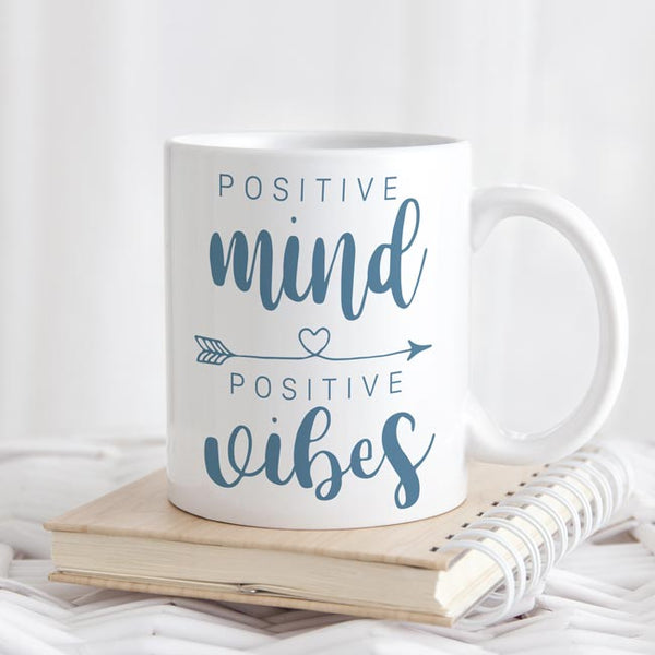 Mug says Positive Mind Positive Vibes with arrow containing heart between the two phrases