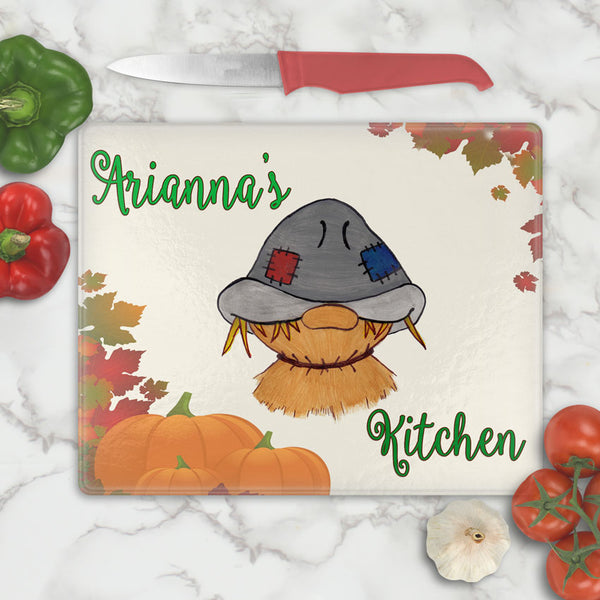 exclusive scarecrow from artist print on a glass cutting board with fall leaves and pumpkins