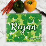 Scatter of Shamrocks fill up the background on a glass cutting board personalized with your name large in the center and an additional line of text small on the bottom right.