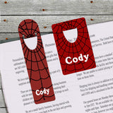Both sizes of spider web bookmark shown holding a book page.